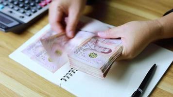 de hand van de schutter telt Thais geld. video