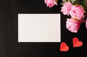 papel blanco y flores rosas pegadas sobre un fondo negro foto