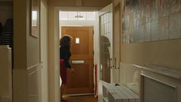 mujer apurada abre y cierra la puerta de entrada corriendo por las escaleras video