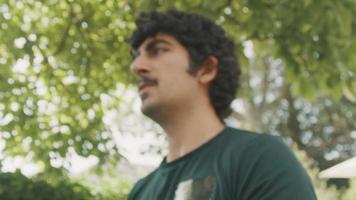 Man standing in garden lifting dumbbells in front of him video