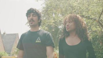 donna e uomo che camminano sul marciapiede mentre conversano video