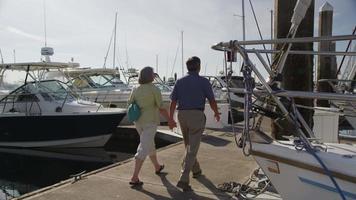 senior paar lopen op dok in de jachthaven. geschoten op rood episch voor hoge kwaliteit 4k, uhd, ultra hd-resolutie. video