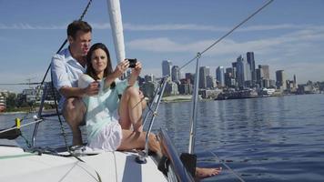 giovane coppia in barca a vela insieme tramite telefono cellulare. girato in rosso epico per una risoluzione 4k, uhd, ultra hd di alta qualità. video