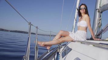jonge vrouw ontspannen op zeilboot. geschoten op rood episch voor hoge kwaliteit 4k, uhd, ultra hd-resolutie. video