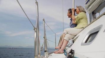 senior paar kijken door een verrekijker op zeilboot samen. geschoten op rood episch voor hoge kwaliteit 4k, uhd, ultra hd-resolutie. video
