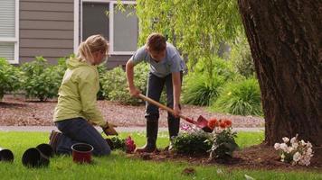 madre e hijo plantando flores en el patio. rodado en rojo épico video