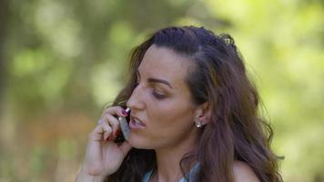 mulher falando ao ar livre no celular video