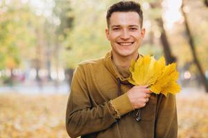 el chico sonriendo y sosteniendo un ramo de hojas de otoño en el parque foto