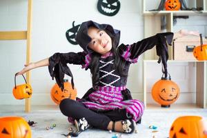 Portrait of little girl with witch dress plays in the room decorated in Halloween festival photo