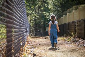 niño caminando por un sendero pasando una valla negra foto