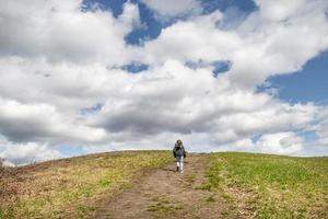 Child walking up a grassy hill toward a cloudy sky photo