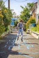 Girl jumping on a hopscotch pattern on a sidewalk in summer photo