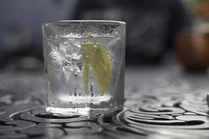 Ice cold gin and tonic in a glass on a table photo