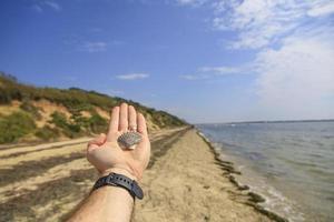 Hand holding a seashell on a sandy beach photo
