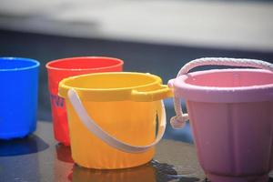Colorful buckets filled with water by a pool photo