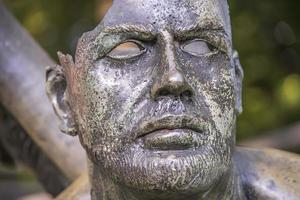 Broken face on a statue in a park, ancient sculpture in Thailand photo