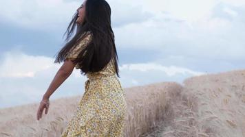 sorglös kvinna njuter av naturen medan hon springer genom ett vetefält. slowmotion 4k -bilder video