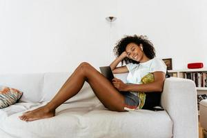 Black young woman in earphones using laptop while resting on sofa photo