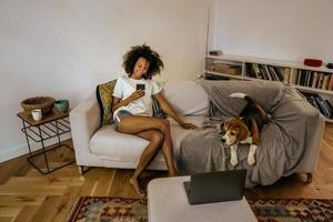 Black young woman using mobile phone while resting with her dog on sofa photo