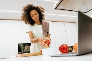 Black young woman making salad while using laptop at kitchen photo
