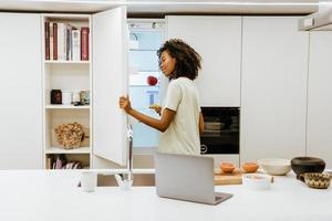 Black young woman opening freezer while making breakfast at kitchen photo