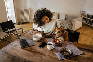 Black young woman stroking her dog while having breakfast photo