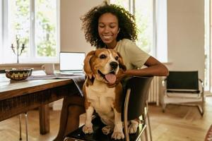 Black young woman stroking her dog while sitting at table photo