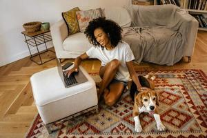 Black woman using laptop and stroking her dog while sitting on floor photo