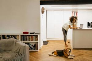 Black young woman using laptop while standing at home photo