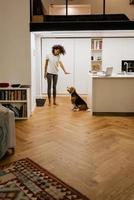 Black young woman smiling while playing with her dog at home photo