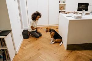 Joven negra en auriculares sonriendo mientras alimenta a su perro foto