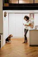 Black young woman having breakfast while looking at her dog in kitchen photo