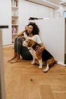 Black young woman stroking her dog while sitting on floor photo