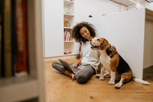 Black young woman using laptop and stroking her dog photo