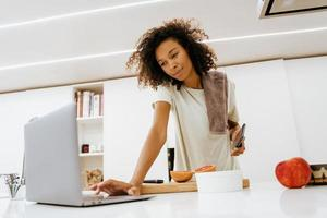 Black young woman using laptop while making breakfast at kitchen photo