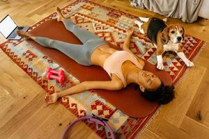 Black young woman lying while resting after yoga practice photo