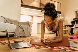 Black young woman using laptop while doing exercise during workout photo
