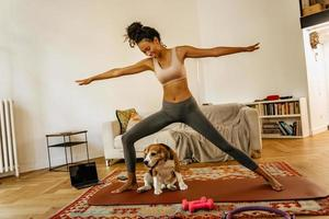 Black young woman doing exercise during yoga practice with her dog photo