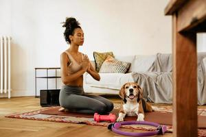 Black young woman meditating during yoga practice with her dog photo