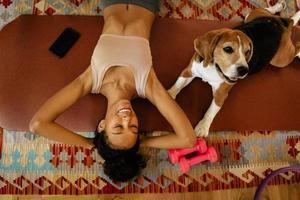 Black young woman laughing while lying with her dog on mat photo