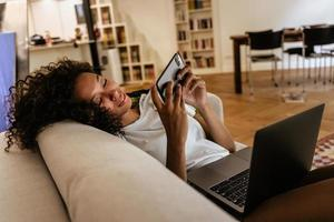 Black young woman using mobile phone and laptop while resting on sofa photo