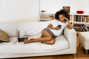 Black young woman using mobile phone while resting on sofa photo