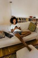 Black young woman in earphones using cellphone while resting on sofa photo