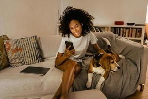 Black young woman using cellphone and stroking her dog on sofa photo