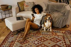 Black woman using cellphone and stroking her dog while sitting on floor photo