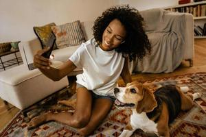 Black woman taking selfie with her dog while sitting on floor photo