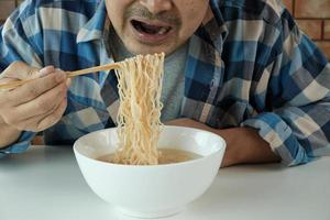 Hungry casual Thai man use chopsticks to eat hot instant noodles in white cup during lunch breaks, quick, tasty, and cheap. Traditional healthy Asian fast food meal of Japanese and Chinese lifestyle. photo