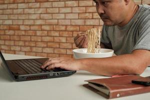 Trabajador tailandés ocupado trabajando con una computadora portátil, use palillos para comer apresuradamente fideos instantáneos durante el almuerzo de la oficina, porque es rápido, sabroso y barato. con el tiempo comida rápida asiática, estilo de vida poco saludable. foto