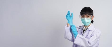 usando guantes. El médico asiático usa guantes de manos de nitrilo de goma azul. foto