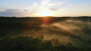 Sun's Rays Illuminate a Light Fog that Descends on the Forest Hills video